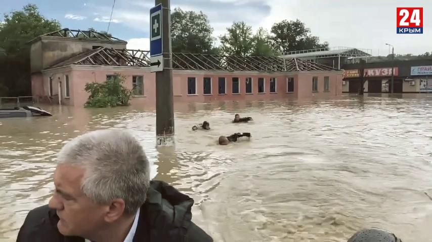 Сергей Аксенов плывет в лодке по затопленной Керчи, а за ним еще трое кролем. Кто эти люди?